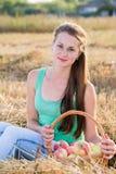 Muchacha adolescente con una cesta de manzanas en campo Imagen de archivo