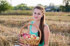 Muchacha adolescente con una cesta de manzanas en campo Fotos de archivo libres de regalías