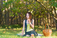 Muchacha adolescente con una cesta en un jardín que come Apple Imágenes de archivo libres de regalías