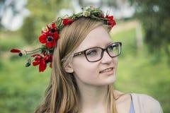 Muchacha adolescente con una guirnalda de amapolas y de margaritas en la cabeza Foto de archivo