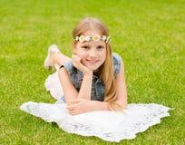 Muchacha adolescente con una guirnalda de las flores que mienten en una hierba verde fresca Imagen de archivo
