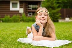 Muchacha adolescente con una guirnalda de las flores que mienten en una hierba verde fresca Fotografía de archivo libre de regalías