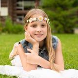 Muchacha adolescente con una guirnalda de las flores que mienten en una hierba verde fresca Fotos de archivo libres de regalías