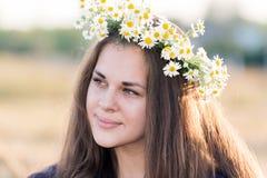 Muchacha adolescente con una guirnalda de margaritas Imagen de archivo
