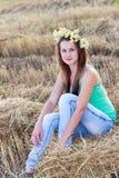 Muchacha adolescente con una guirnalda de margaritas en campo Foto de archivo