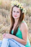 Muchacha adolescente con una guirnalda de margaritas en campo Fotografía de archivo libre de regalías
