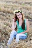 Muchacha adolescente con una guirnalda de margaritas en campo Fotografía de archivo