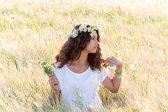 Muchacha adolescente con una guirnalda de margaritas en campo Imágenes de archivo libres de regalías