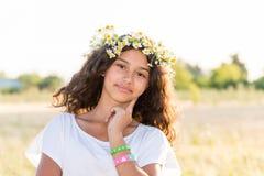 Muchacha adolescente con una guirnalda de margaritas en campo Imagenes de archivo