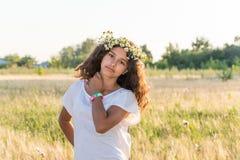Muchacha adolescente con una guirnalda de margaritas en campo Foto de archivo libre de regalías