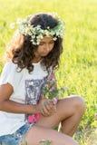 Muchacha adolescente con una guirnalda de margaritas en campo Fotos de archivo