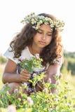 Muchacha adolescente con una guirnalda de margaritas en campo Imagen de archivo libre de regalías