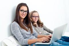Muchacha adolescente con una hermana más joven en cama con los ordenadores portátiles Fotografía de archivo libre de regalías