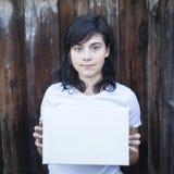 Muchacha adolescente con una hoja blanca en sus manos Fotografía de archivo