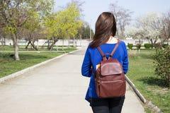 Muchacha adolescente con una mochila en el camino Fotos de archivo libres de regalías
