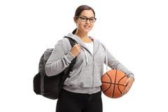 Muchacha adolescente con una mochila y un baloncesto Foto de archivo