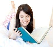 Muchacha adolescente confidente que estudia la mentira en una cama Imágenes de archivo libres de regalías