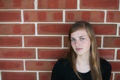 Muchacha adolescente contra la pared de ladrillo Fotos de archivo libres de regalías