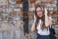 Muchacha adolescente contra una pared de ladrillo que escucha la música en auriculares Fotografía de archivo libre de regalías