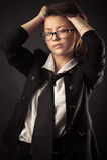 Muchacha adolescente coreana en el traje de negocios que sostiene el pelo de las manos Fotos de archivo