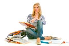 Muchacha adolescente dada una sacudida eléctrica que señala en libro escolar abierto Imagenes de archivo