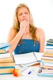 Muchacha adolescente de bostezo que se sienta en el vector con los libros Fotos de archivo libres de regalías