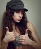 Muchacha adolescente de la alegría feliz en casquillo de la moda con el pulgar para arriba Foto de archivo libre de regalías