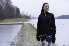 Muchacha adolescente de la aptitud caucásica sueca hermosa que se coloca en el puente de madera al aire libre en paisaje del invi Foto de archivo