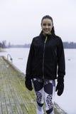 Muchacha adolescente de la aptitud caucásica sueca hermosa que se coloca en el puente de madera al aire libre en paisaje del invi Fotos de archivo libres de regalías