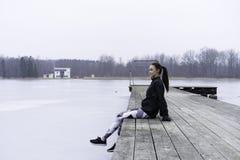 Muchacha adolescente de la aptitud caucásica sueca hermosa que se sienta en el puente de madera Fotografía de archivo