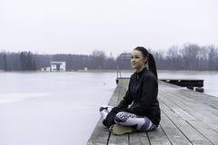 Muchacha adolescente de la aptitud caucásica sueca hermosa que se sienta en el puente de madera al aire libre en paisaje del invi Imagen de archivo