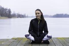 Muchacha adolescente de la aptitud caucásica sueca hermosa que se sienta en el puente de madera al aire libre en paisaje del invi Imágenes de archivo libres de regalías
