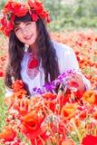 Muchacha adolescente de la belleza en el campo de amapolas rojas Imagenes de archivo