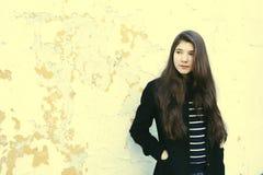 Muchacha adolescente de la moda en capa negra y calle marrón larga del pelo Imagen de archivo