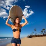 Muchacha adolescente de la persona que practica surf morena que sostiene la tabla hawaiana en una playa Imagen de archivo