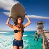 Muchacha adolescente de la persona que practica surf morena que sostiene la tabla hawaiana en una playa Imagen de archivo libre de regalías