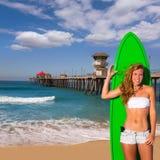 Muchacha adolescente de la persona que practica surf rubia que sostiene la tabla hawaiana en la playa Foto de archivo libre de regalías