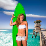 Muchacha adolescente de la persona que practica surf rubia que sostiene la tabla hawaiana en la playa Foto de archivo