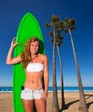 Muchacha adolescente de la persona que practica surf rubia que sostiene la tabla hawaiana en la playa Fotografía de archivo