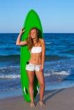 Muchacha adolescente de la persona que practica surf rubia que sostiene la tabla hawaiana en la playa Fotos de archivo libres de regalías