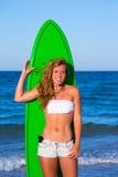 Muchacha adolescente de la persona que practica surf rubia que sostiene la tabla hawaiana en la playa Imágenes de archivo libres de regalías