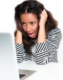 Muchacha adolescente de la raza mezclada, dada una sacudida eléctrica mirando la computadora portátil Fotos de archivo