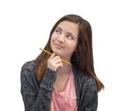Muchacha adolescente de la raza mixta linda que piensa con el lápiz Fotografía de archivo libre de regalías