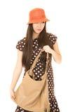 Muchacha adolescente de la raza mixta linda que sostiene su monedero que lleva una ha anaranjada Imagen de archivo