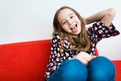 Muchacha adolescente de los años que se sienta y que sonríe en el sofá rojo fotos de archivo