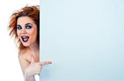 Muchacha adolescente de mirada divertida detrás de la pared Imagenes de archivo