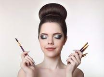 Muchacha adolescente de Pretty del artista de maquillaje con el peinado y la molestia lindos del bollo Imagen de archivo libre de regalías