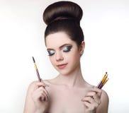 Muchacha adolescente de Pretty del artista de maquillaje con el peinado y la molestia lindos del bollo Imagenes de archivo