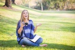 Muchacha adolescente de risa con el libro y el teléfono celular al aire libre Foto de archivo