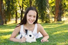 Muchacha adolescente de risa hermosa linda con el conejo negro blanco del bebé Imágenes de archivo libres de regalías